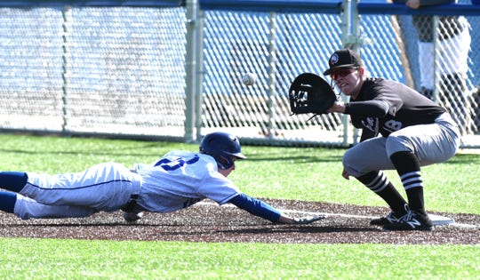 Catholic Central player Adam Falinski safely slides back to first base ahead of a tag by Brother Rice's Sterling Hallman.