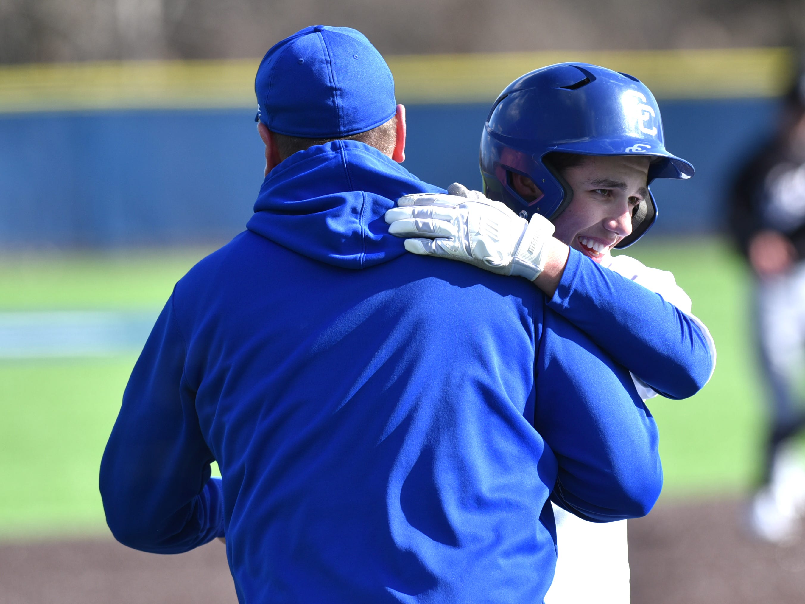 Shamrock Cooper Donlin is congratulated by his CC third base coach after bringing in some runs with a triple.