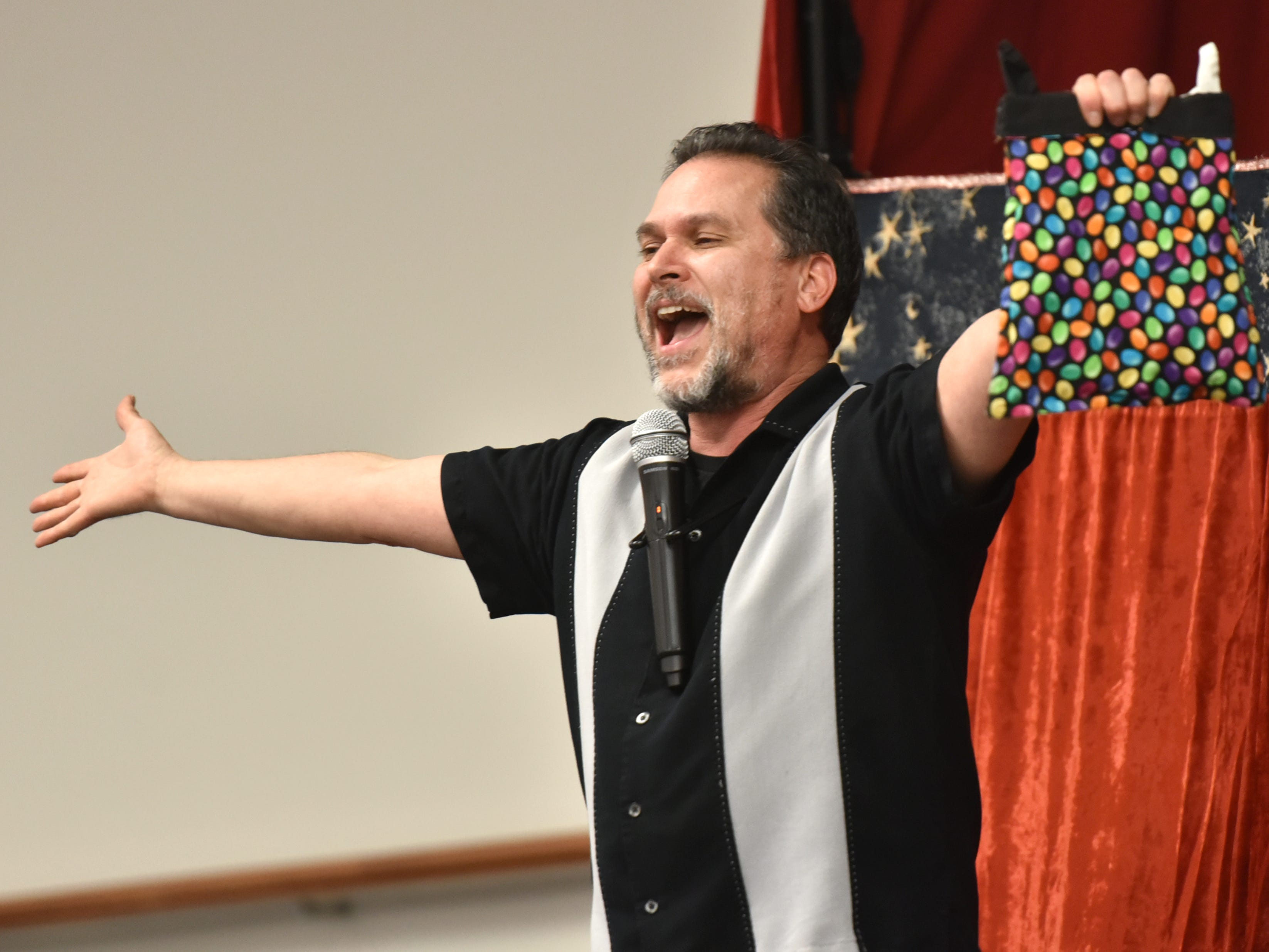 """Eugene Clark does a """"tah-dah"""" move as he finishes a magic trick for his April 2 audience at the Farmington Hills Library. Clark was also there to do a puppet show called Jo-Jo Fish and the Magic Pearl."""