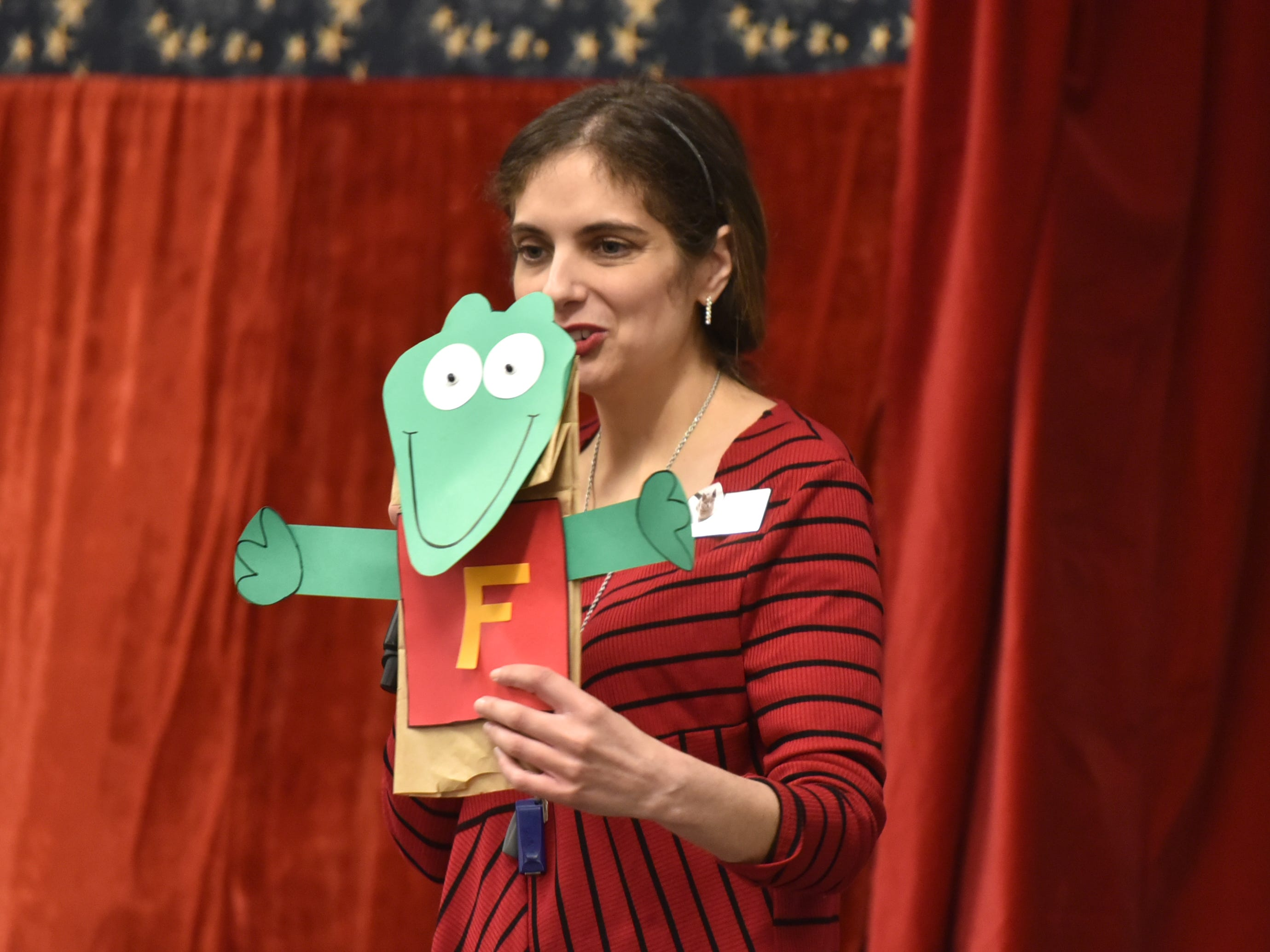 Farmington Hills Librarian Jennifer Harper shows off the paper bag puppet kits the library will give away to attendees of the April 2 Amazing Clark puppet show.