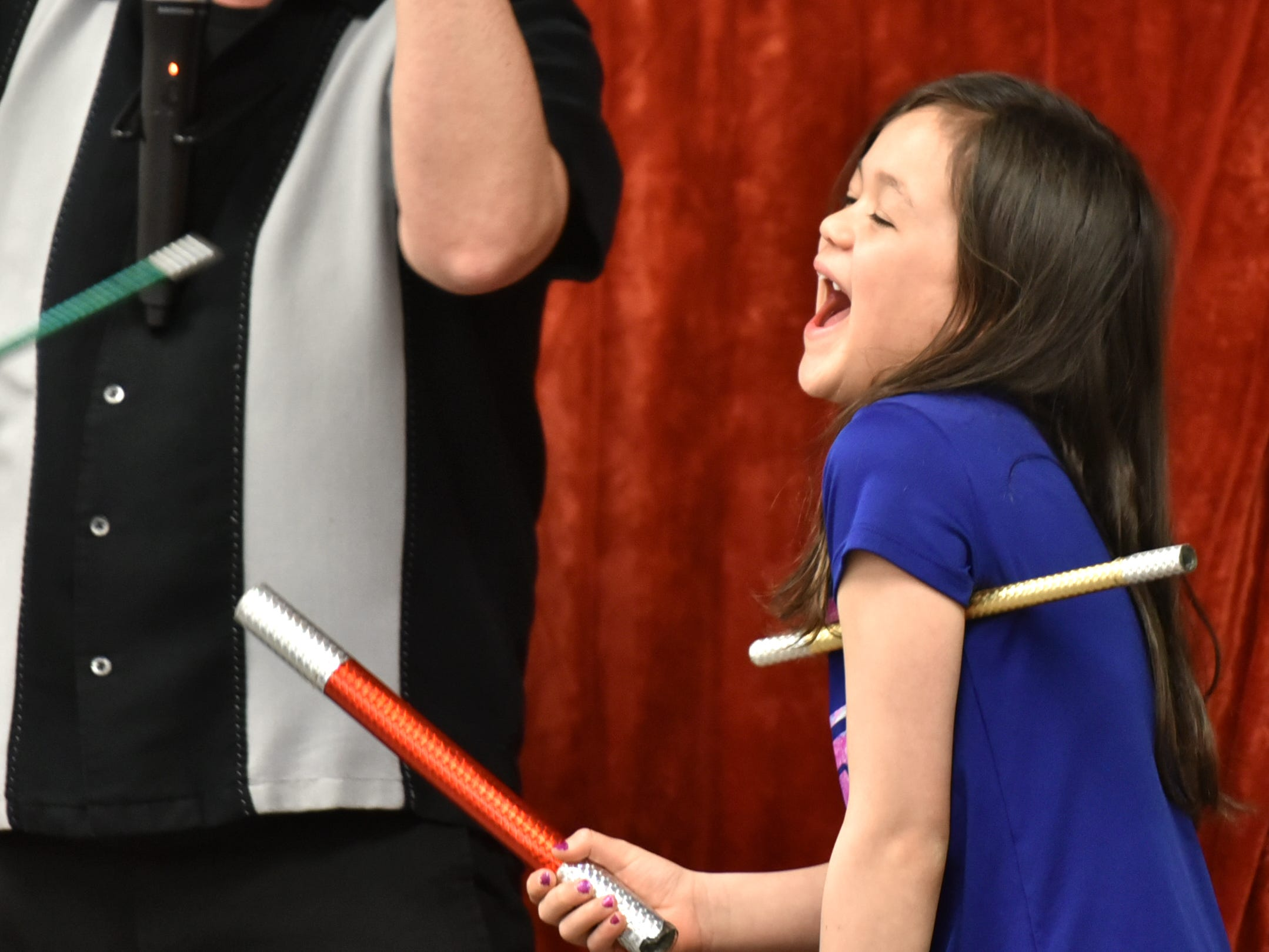 After getting more magic wands than she knows what to do with from Eugene Clark, left, and running out of hands to hold them in, Persephone Baglieri, 8, laughs out loud at her predicament.