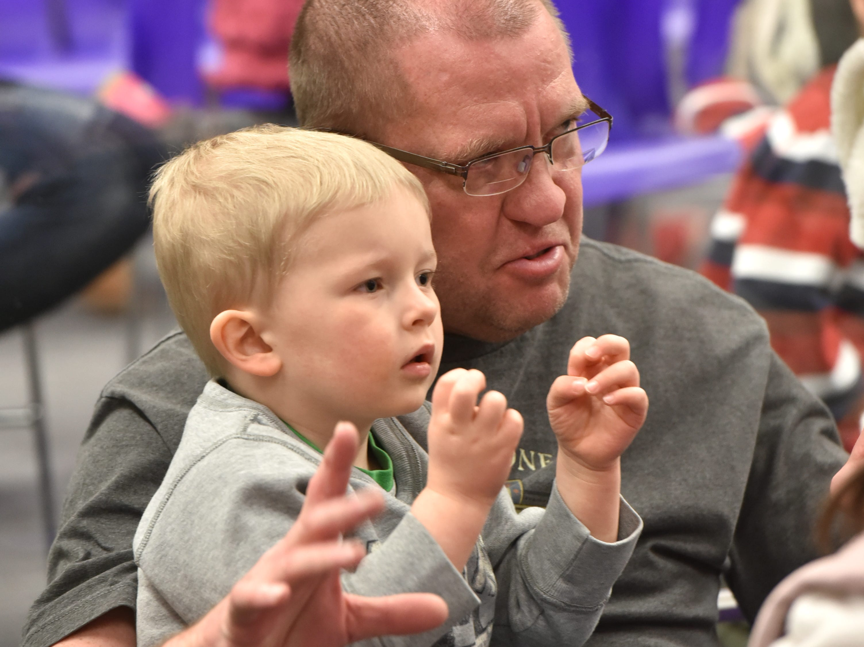 Joie Kramer and his grandson Finley Deppe, 3, work some magic hands to go along with Eugene Clark's show at the library.