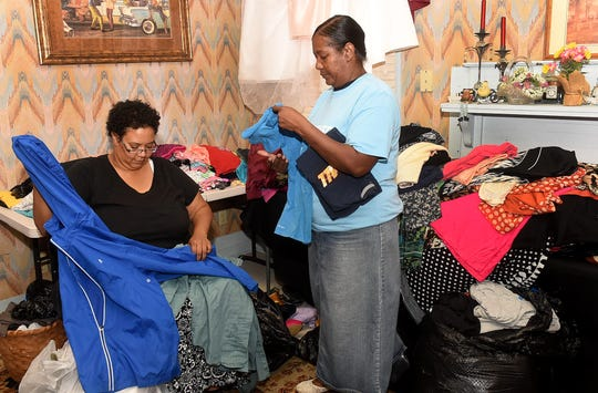 Opelousas residents Sarah Broussard and Letoria Castille gather up used clothing to be donated to a Breaux Bridge family that lost all their belongings in a house fire.