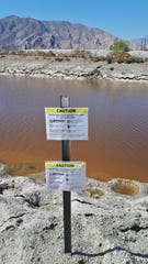 Warning signs along an inlet warn people stay away from algae if it's visible in the water at the Salton Sea.