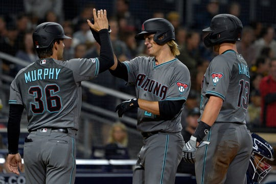 Apr 2, 2019: Arizona Diamondbacks starting pitcher Zack Greinke (middle) celebrates with catcher John Ryan Murphy (36) and shortstop Nick Ahmed (13) after hitting a three run home run against the San Diego Padres during the fourth inning at Petco Park.