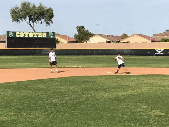 Skyline baseball players fields groundouts at second base and shortshop positions during practice