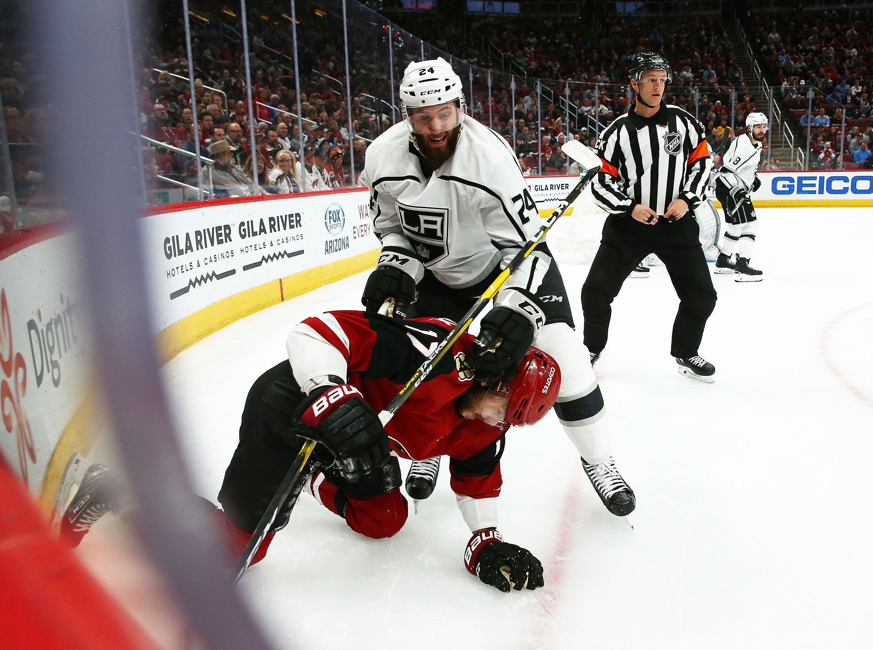 Los Angeles Kings defenseman Derek Forbort (24) pushes Arizona Coyotes center Alex Galchenyuk (17) to the ice in the second period on Apr. 2, 2019 at Gila River Arena in Glendale, Ariz.