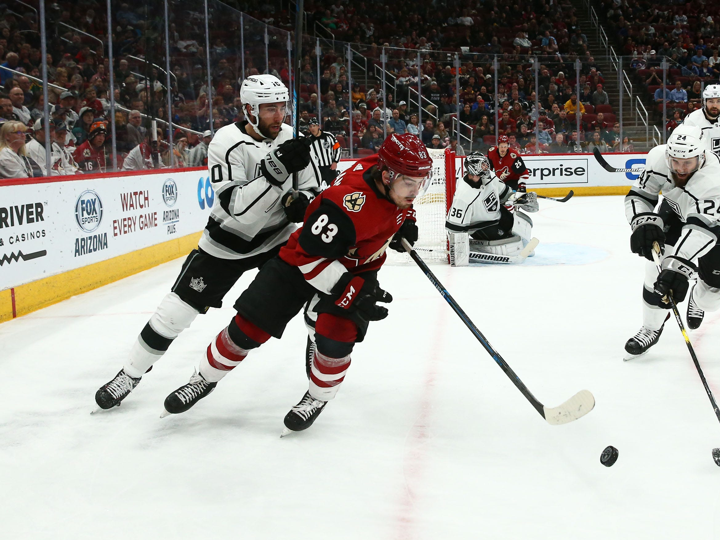 Arizona Coyotes right wing Conor Garland (83) battles for the puck with Los Angeles Kings defenseman Derek Forbort (24) in the second period on Apr. 2, 2019 at Gila River Arena in Glendale, Ariz.