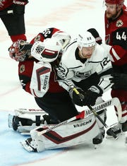 Coyotes goaltender Darcy Kuemper (35) takes a stick to the face from Kings center Trevor Lewis (22) after Lewis scored in the third period on Tuesday.