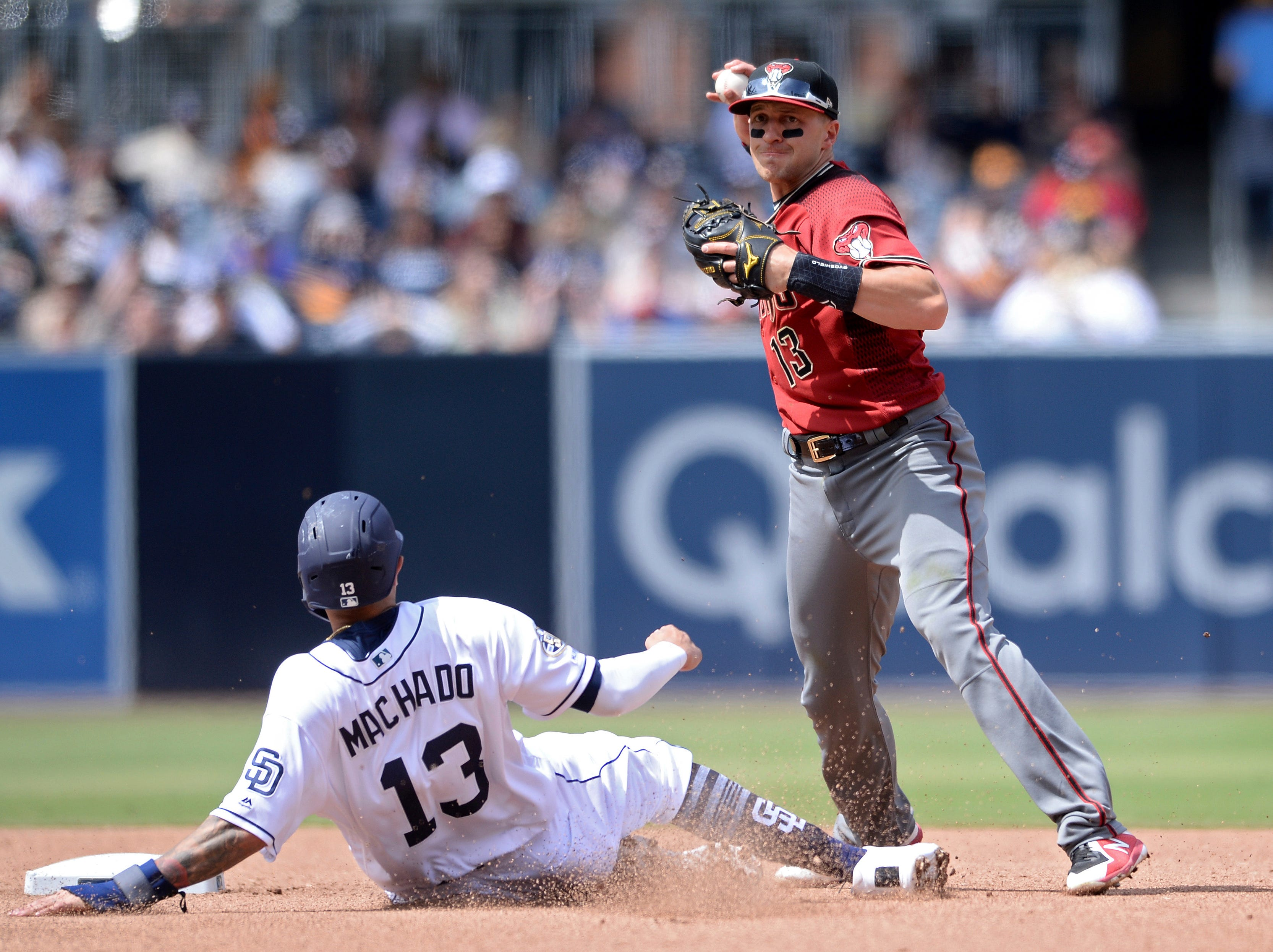 Arizona Diamondbacks shortstop Nick Ahmed forces out San Diego Padres' Manny Machado at second base before throwing to first base to complete the double play on a ball hit by Franmil Reyes during the fourth inning of a baseball game Wednesday, April 3, 2019, in San Diego. (AP Photo/Orlando Ramirez)