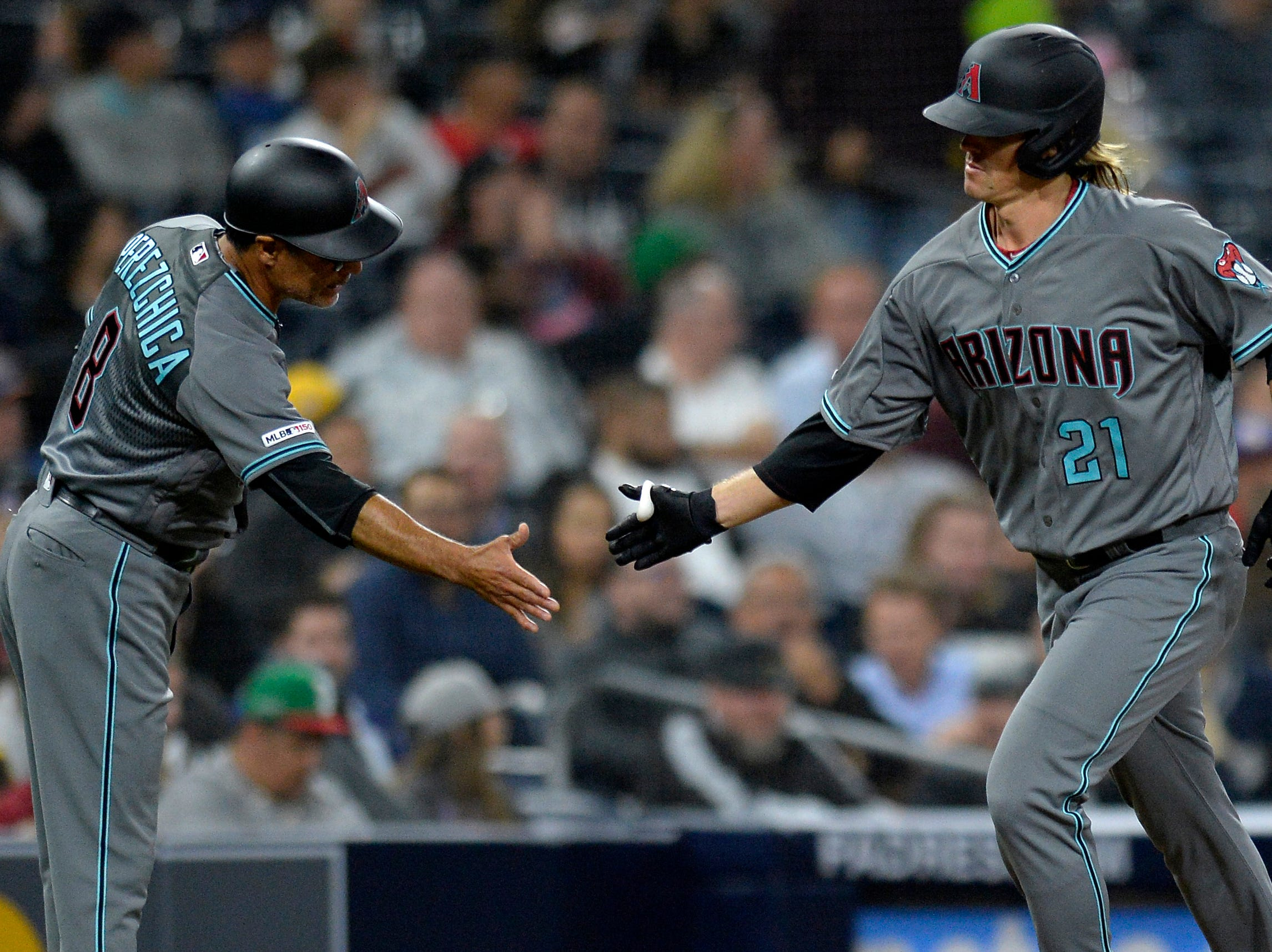 Apr 2, 2019; San Diego, CA, USA; Arizona Diamondbacks starting pitcher Zack Greinke (21) is congratulated by third base coach Tony Perezchica (8) after hitting his second home run of the game during the sixth inning against the San Diego Padres at Petco Park. Mandatory Credit: Jake Roth-USA TODAY Sports
