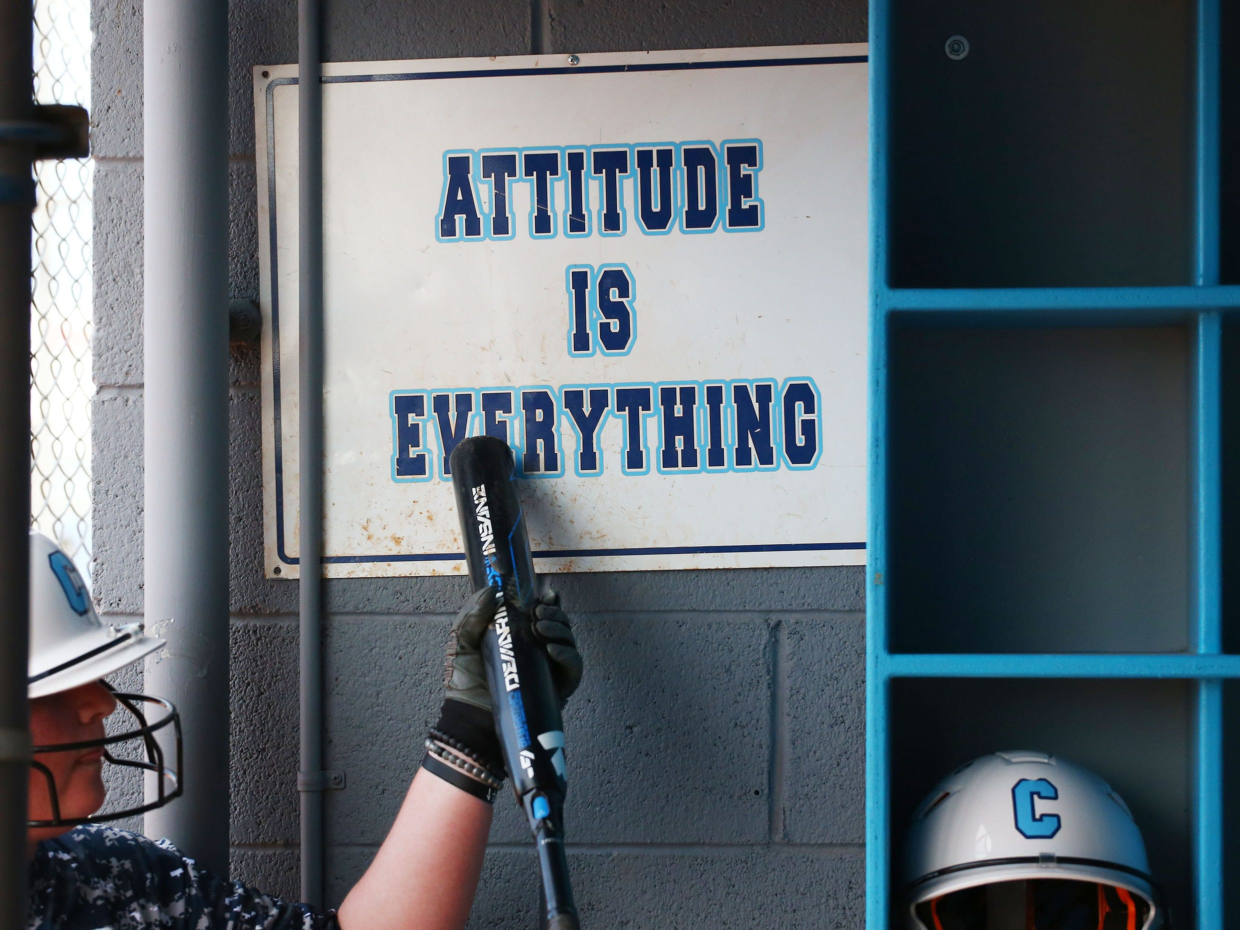 Cactus High softball player McKenna Feringa taps her bat on the 'Attitude Is Everything' sign in the dugout during practice on Apr. 2, 2019 at Cactus High School in Glendale, Ariz.