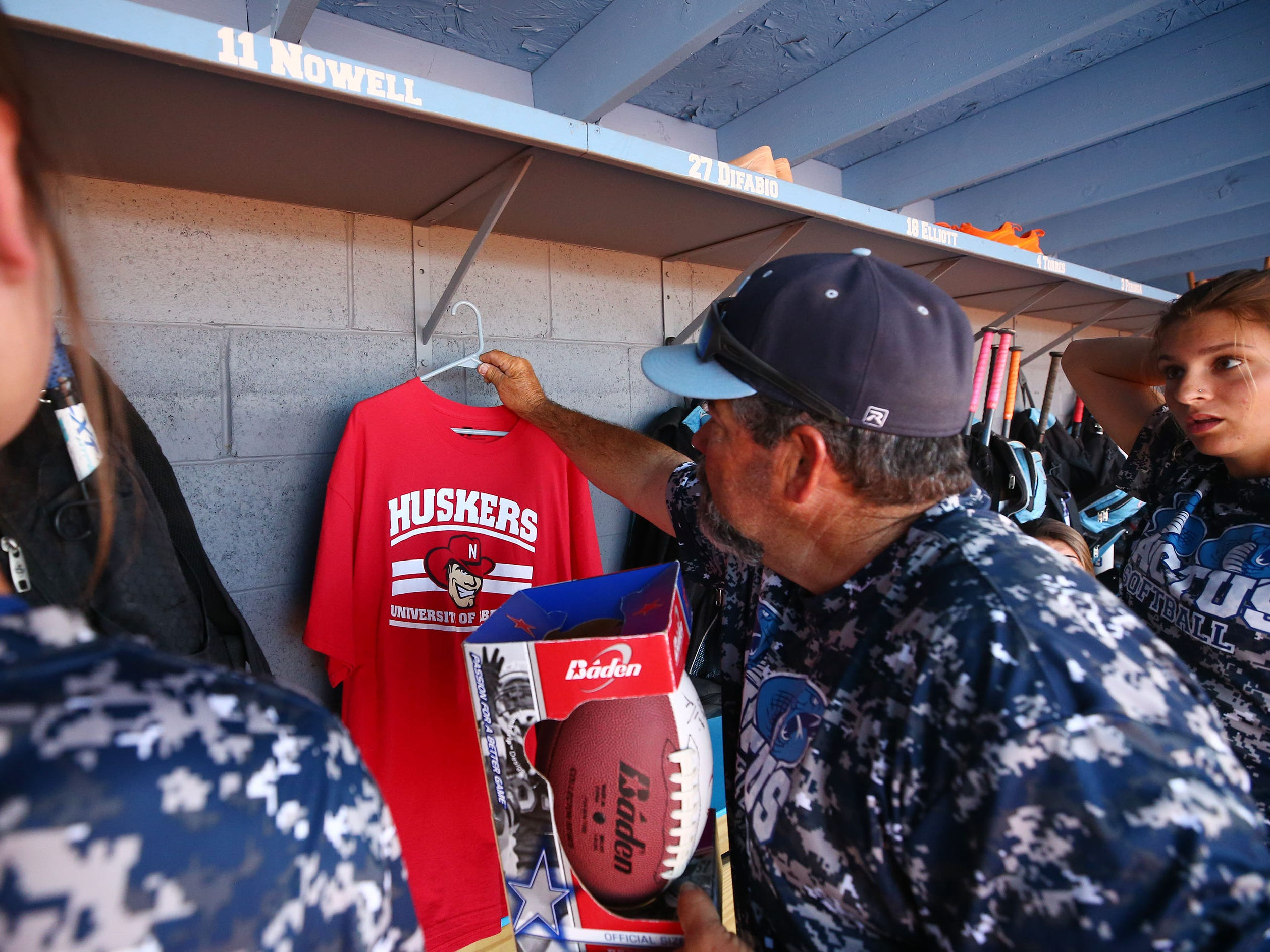 Cactus High softball coach Bartt Underwood hangs a Nebraska shirt in the dugout to honor their former booster club president Dan Renyer, who died last December, during a Cactus High softball practice on Apr. 2, 2019 at Cactus High School in Glendale, Ariz.