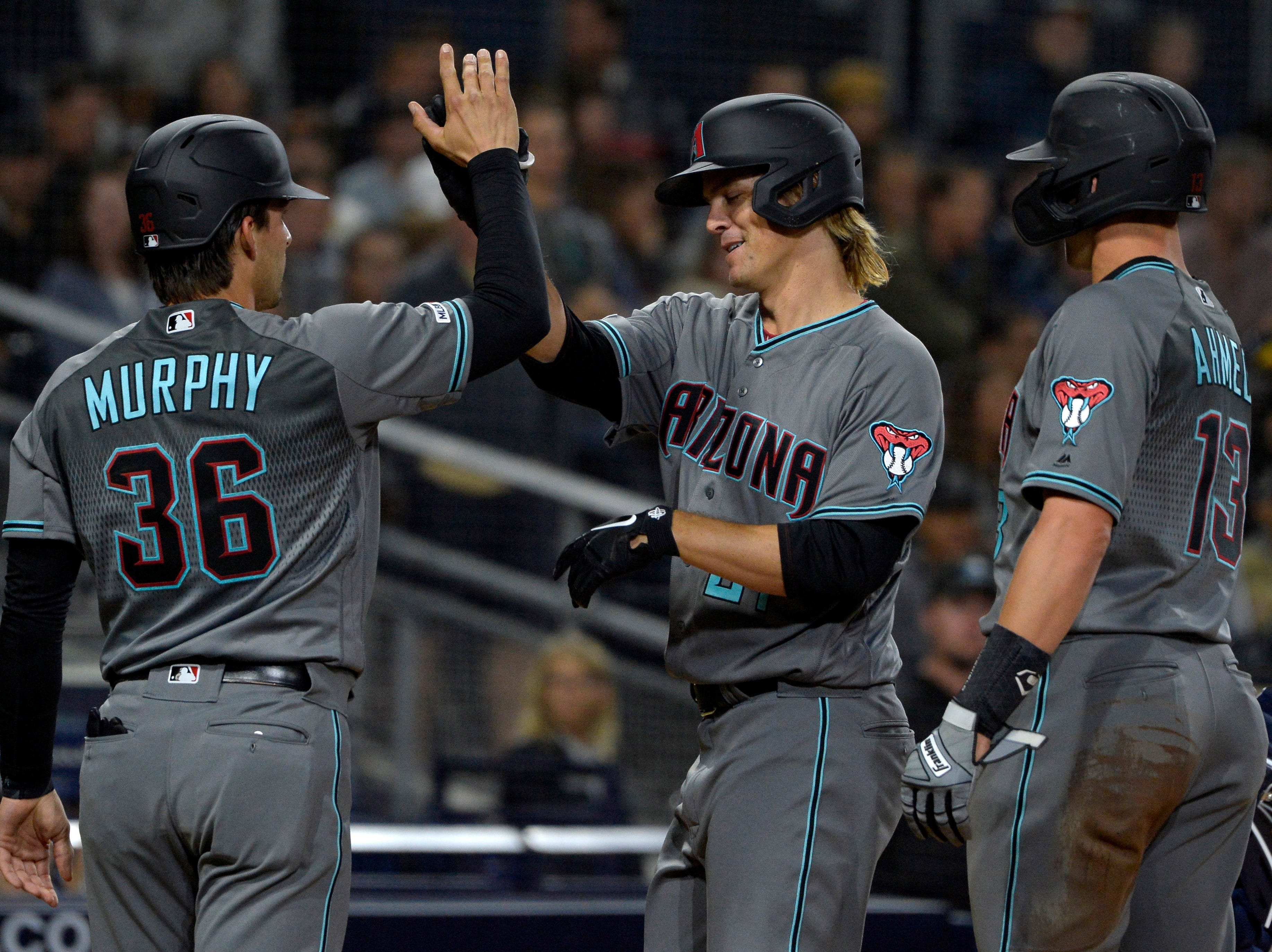 Apr 2, 2019; San Diego, CA, USA; Arizona Diamondbacks starting pitcher Zack Greinke (middle) celebrates with catcher John Ryan Murphy (36) and shortstop Nick Ahmed (13) after hitting a three run home run against the San Diego Padres during the fourth inning at Petco Park. Mandatory Credit: Jake Roth-USA TODAY Sports