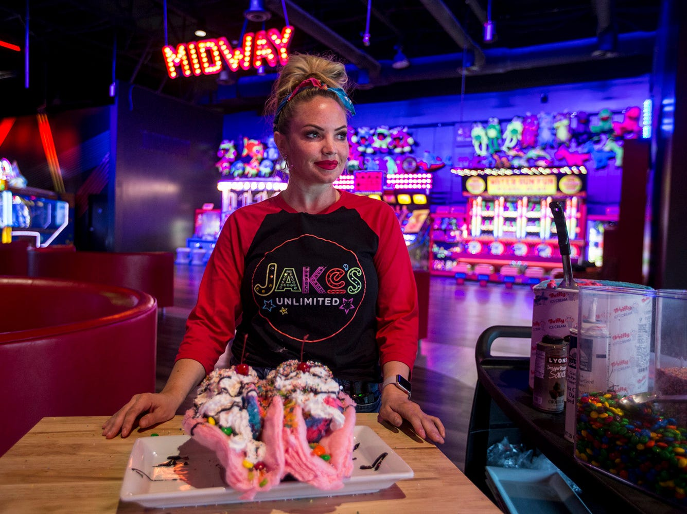 Lacey Hall poses for a portrait with Unicorn Tacos on Monday, Apr. 1, 2019, at Jake's Unlimited in Mesa, Ariz. The dessert is made with a cotton candy shell, ice cream, cereal, sprinkles, M&M's, whipped cream, chocolate sauce, and cherries.
