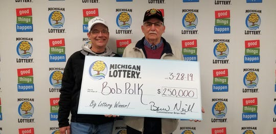 St. Clair resident Bob Polk, right, stands with his stepson, Bryan, after collecting Bob's $250,000 prize in March 2019.