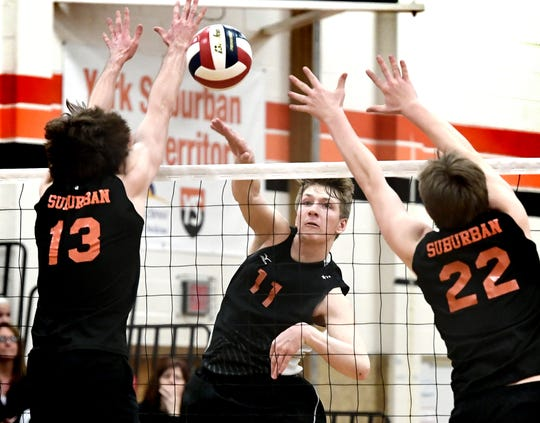 Central York's Braden Richard gets a slam past York Suburban's Nate Bowman, left, and John Doll during volleyball action at Suburban on Tuesday, April 2, 2019. Central won the match 3-1. Richard is one of the key performers on the powerhouse Panthers team. Bill Kalina photo