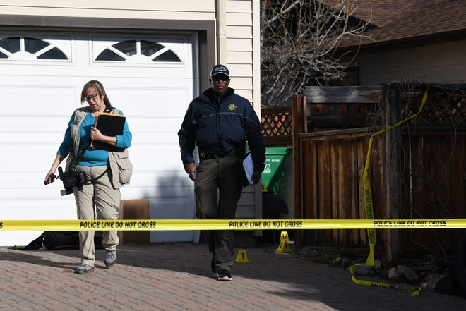 Reno Police Department investigators walk in front of a home on the 1000 block of Crown Drive in north Reno on Wednesday, April 3. Police are investigating a homicide at the residence after a body was found outside the home the night before.