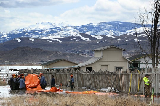 Washoe County installs temporary inflatable barriers, called Tiger Dams, in front of homes bordering Swan Lake along Shane Way in Lemmon Valley on April 3, 2019.
