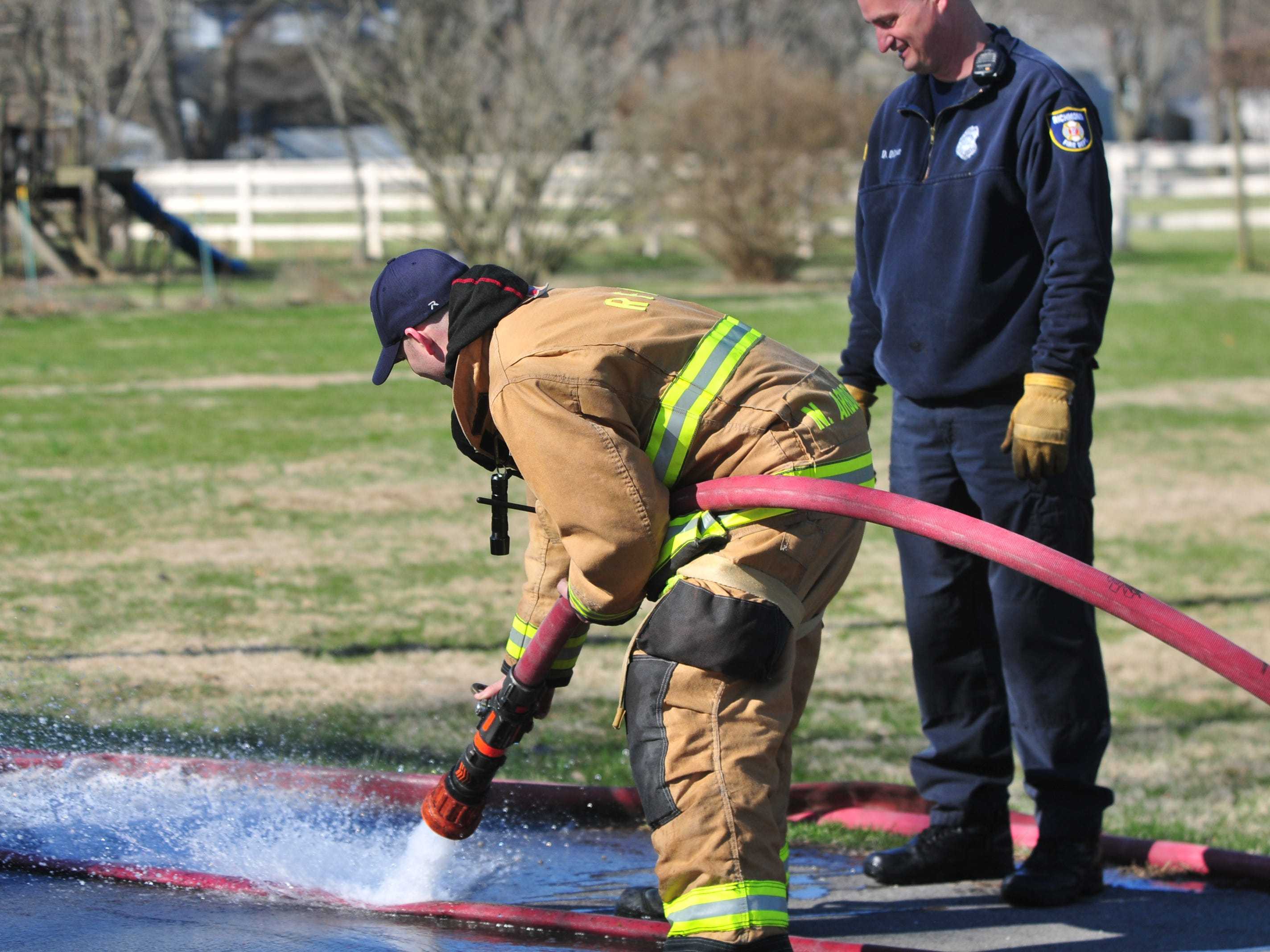 A hose is cleaned Wednesday morning after a house fire was extinguished in the 2100 block of South 11th Street.