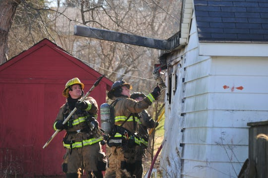 Richmond Fire Department personnel tears away burned areas of a house looking for fire Wednesday morning in the 2100 block of South 11th Street.