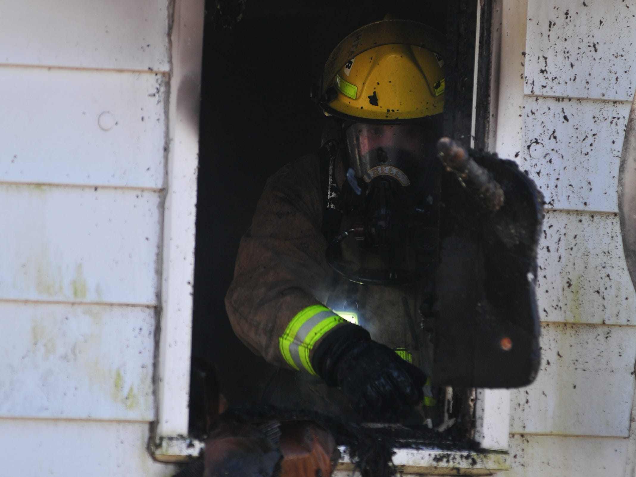 Burned material is tossed out a window of a house in the 2100 block of South 11th Street.