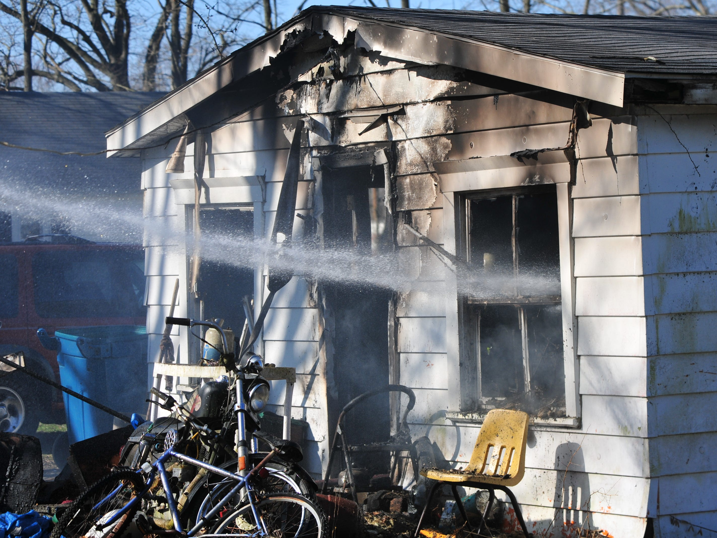 A water stream exits through the window of a house Wednesday morning as Richmond Fire Department personnel extinguishes a fire.
