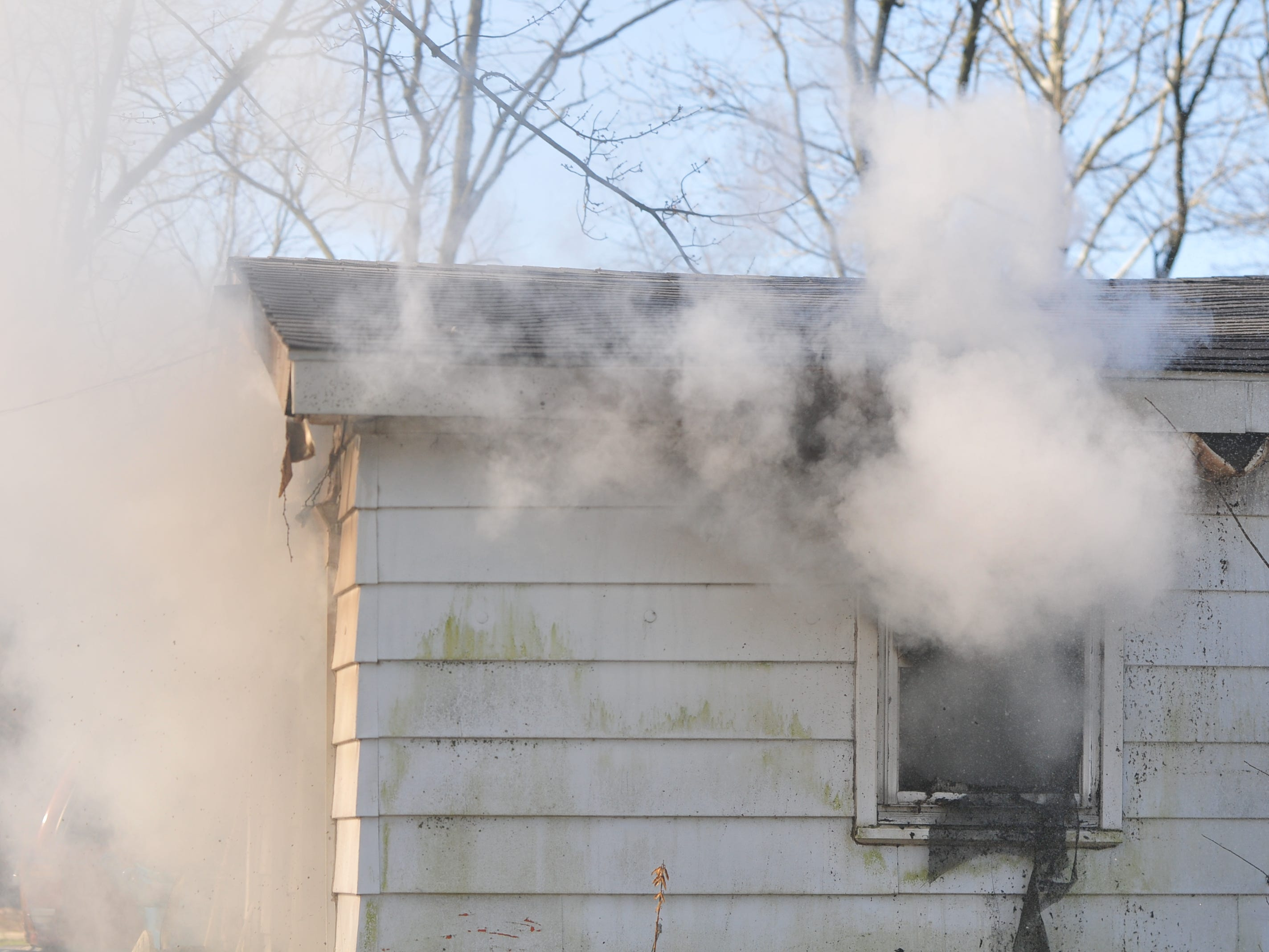 Smoke pours from a house in the 2100 block of South 11th Street on Wednesday morning.