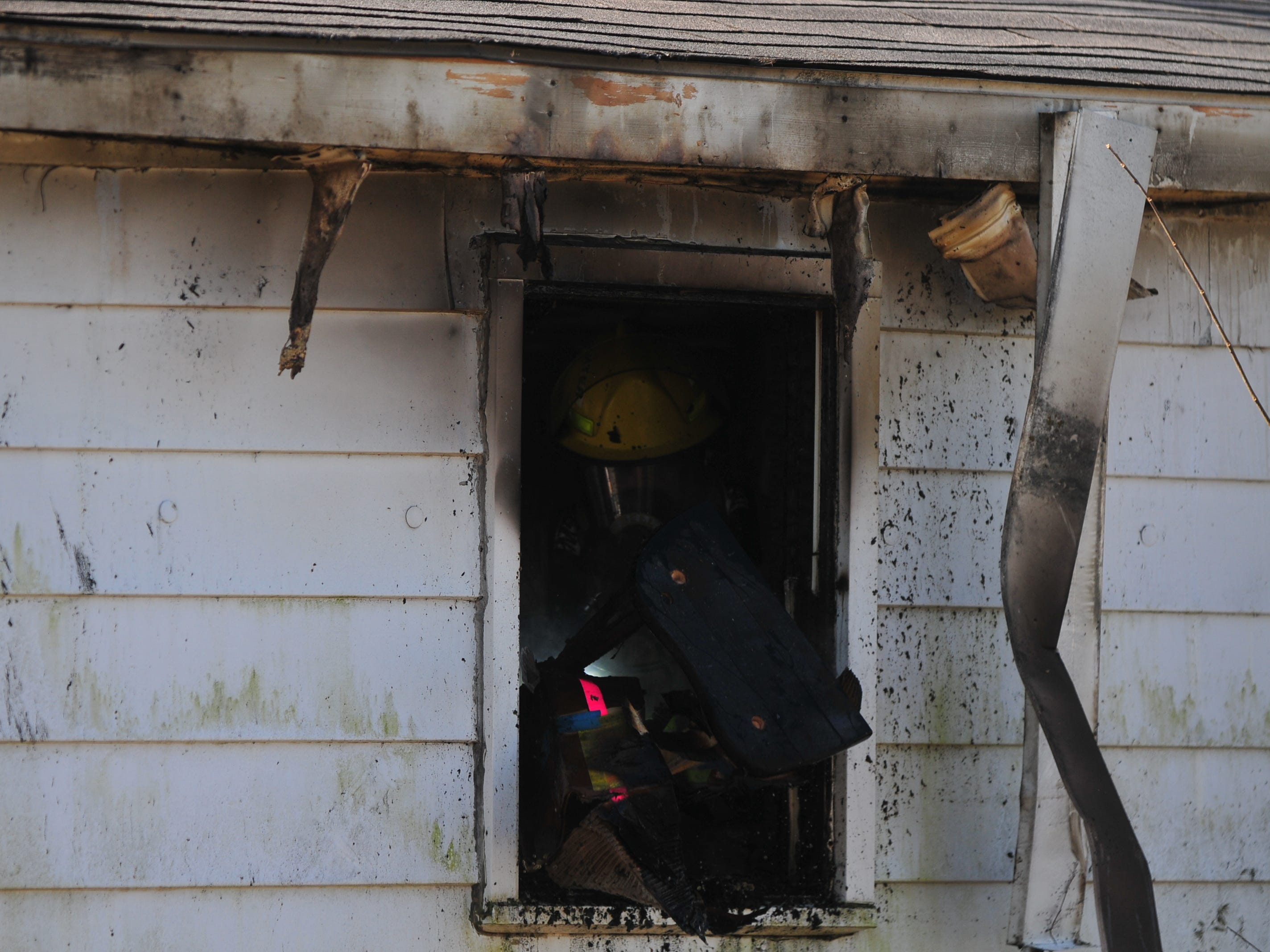 Burned material is tossed out a window Wednesday morning at a house in the 2100 block of South 11th Street.
