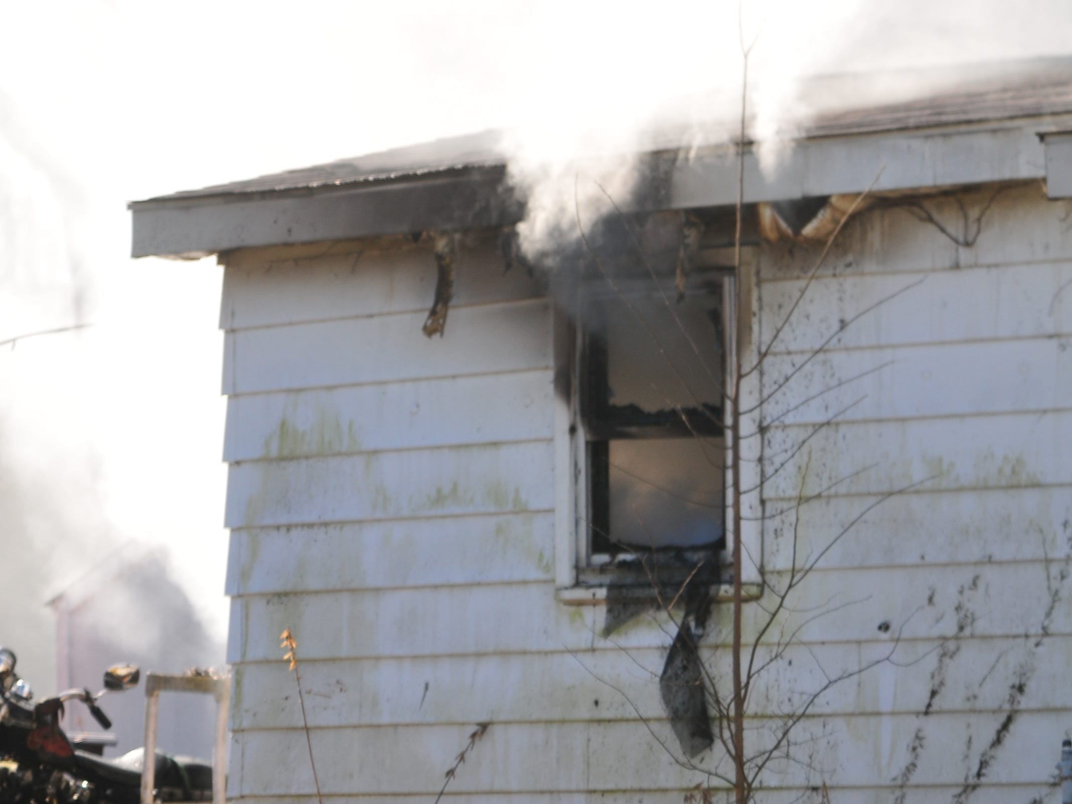 Smoke escapes through a window of a home in the 2100 block of South 11th Street.