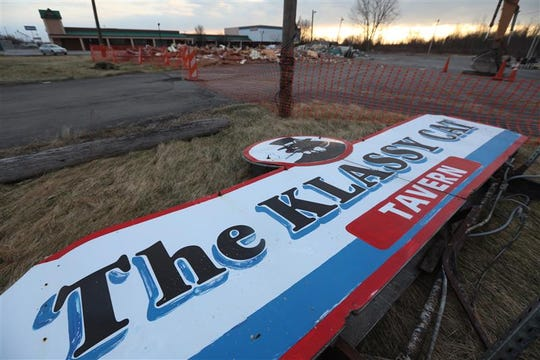 The business sign for The Klassy Cat Tavern is near what's left the of former strip club in Henrietta. The building was razed this week.