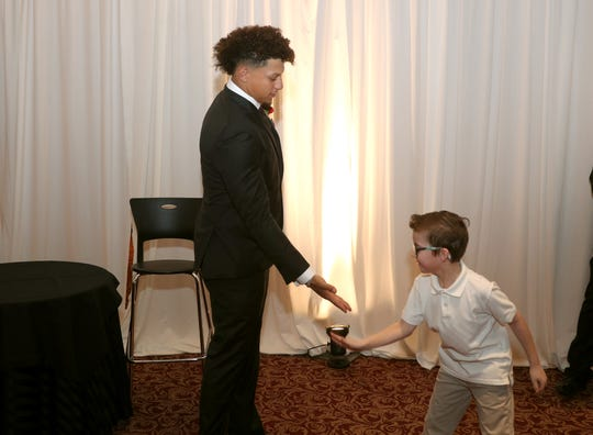 Kansas City Chiefs quarterback Patrick Mahomes gets a low five from 8-year-old DJ Whalen before the Rochester Press-Radio Club Day of Champions Dinner.