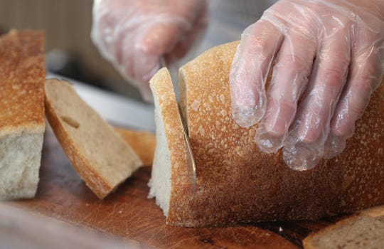 Alla Fedorishina slices a loaf of bread at her Spencerport bakery.
