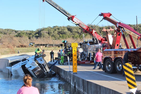Crews pull out a truck hauling 42,000 pounds of avocados that overturned into the South Llano River Feb. 15, 2019, at the bridge on US 377.