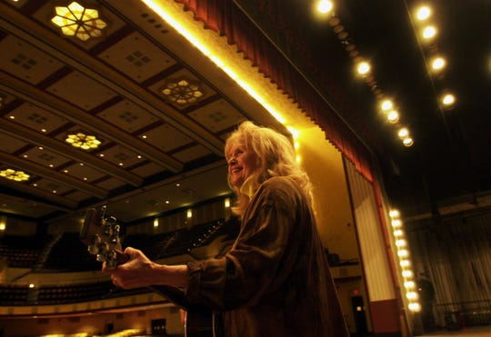 -  -F.A.M.E. co-founder Maggie Warwick warms up on her guitar before playing for a group of journalists at the Municipal Auditorium.-  -Times Photo/Charlie Gesell 4/23/02