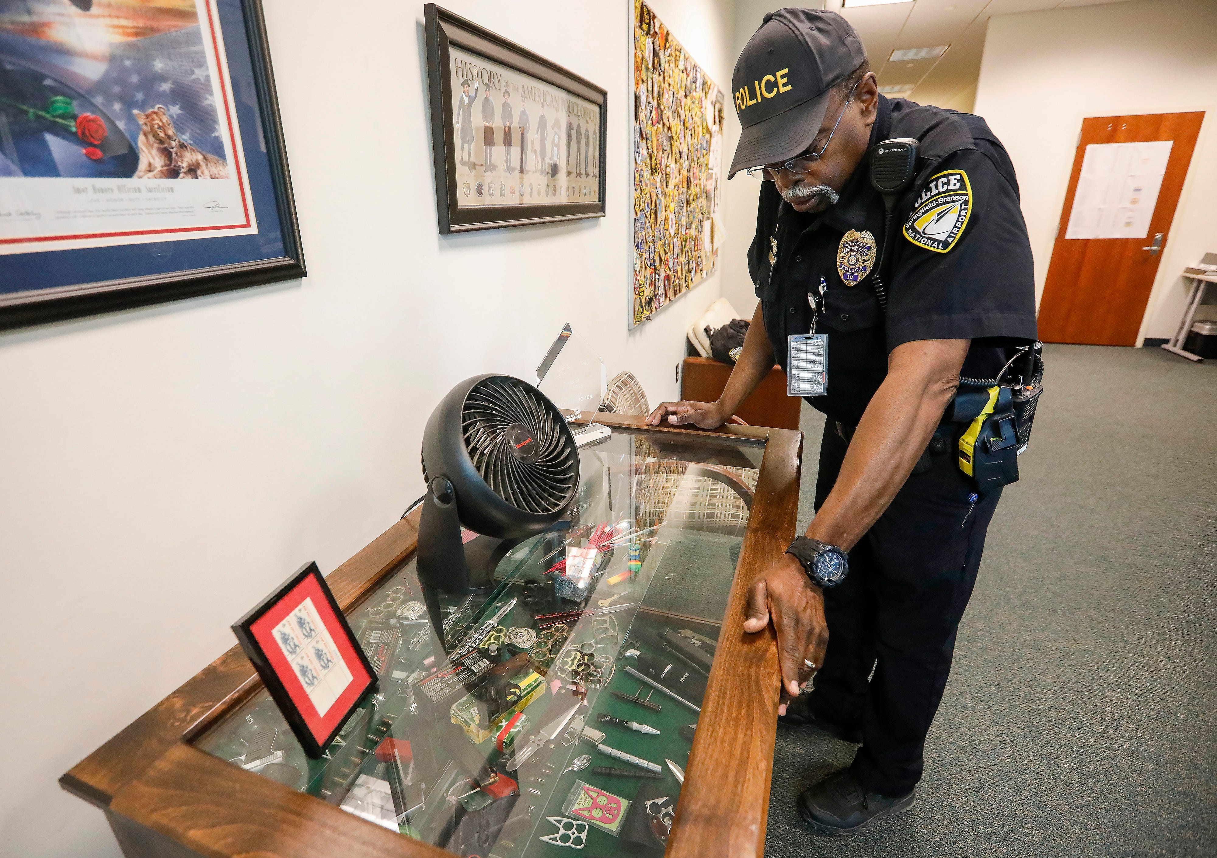 Al Berry, a police officer at the Springfield-Branson National Airport, looks at items that have been confiscated from passengers.