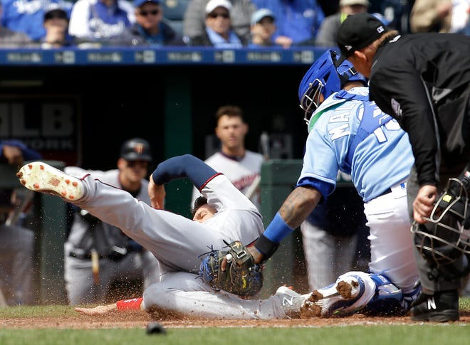 Minnesota Twins' Jake Cave (60) is tagged out at home by Kansas City Royals catcher Martin Maldonado as he tried to score on an RBI double by Mitch Garver during the fourth inning of a baseball game Wednesday, April 3, 2019, in Kansas City, Mo. (AP Photo/Charlie Riedel)