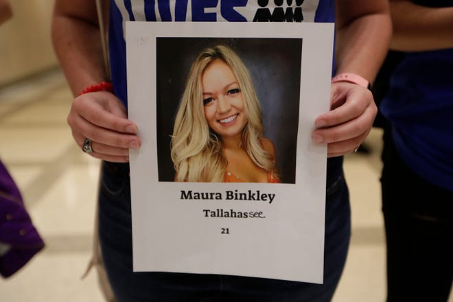 A March for Our Lives advocate holds a photo of Maura Binkley, a victim of the Tallahassee Hot Yoga shooting, in this 2019 file photo.