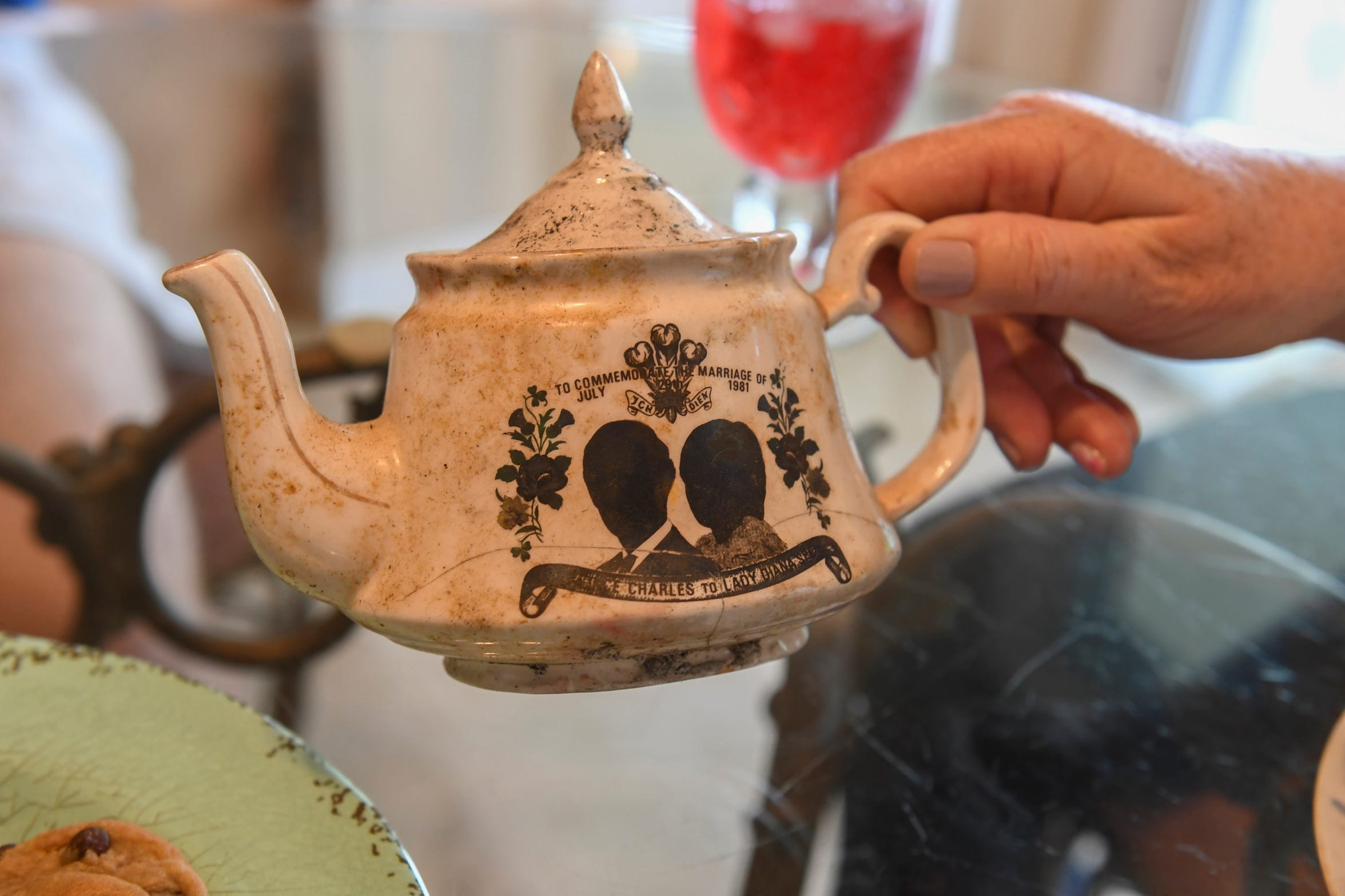 Linda Boogaart holds a teapot, part of a commemorative tea set from the marriage of Prince Charles and Princess Diana, recovered from the remains of their home. It still shows the damage and ashes of the fire that destroyed their home April 15, 1999, in Port St. Lucie.