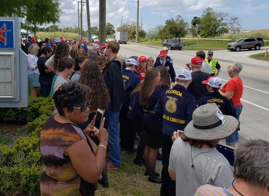 Dozens of Make Lake O Great Again hats dot the crowd of onlookers assembled to see President Donald Trump arrive in Canal Point.