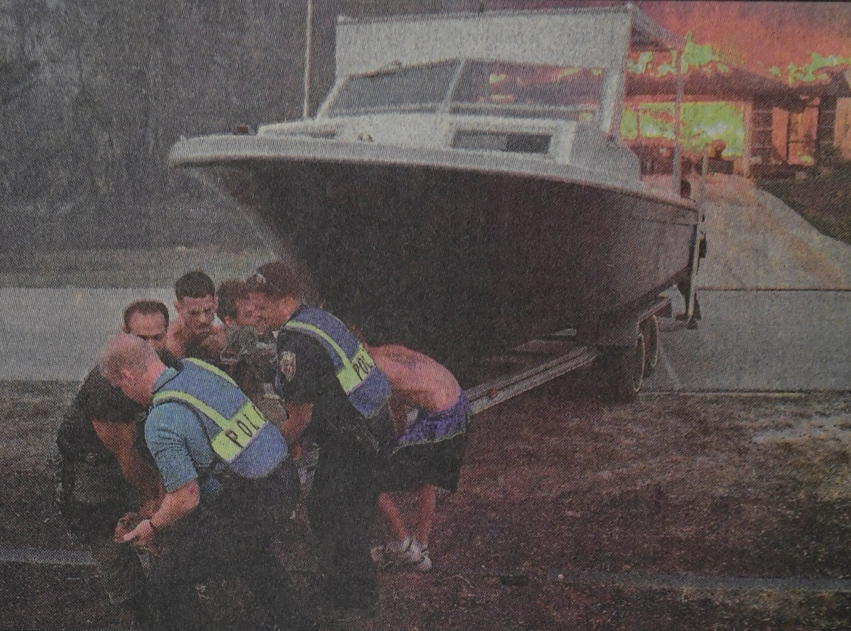 Port St. Lucie police officers and neighbors remove a boat from the driveway of a burning home on Grandberry Street April 15, 1999, in Port St. Lucie.