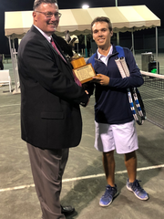 John Martinelli, vice president at Natalie's Orchid Island Juice Co., left, presents Chase Perez-Blanco, of Quail Valley River Club, with the King of Hill 2019 Youth Guidance Tennis Tournament trophy.