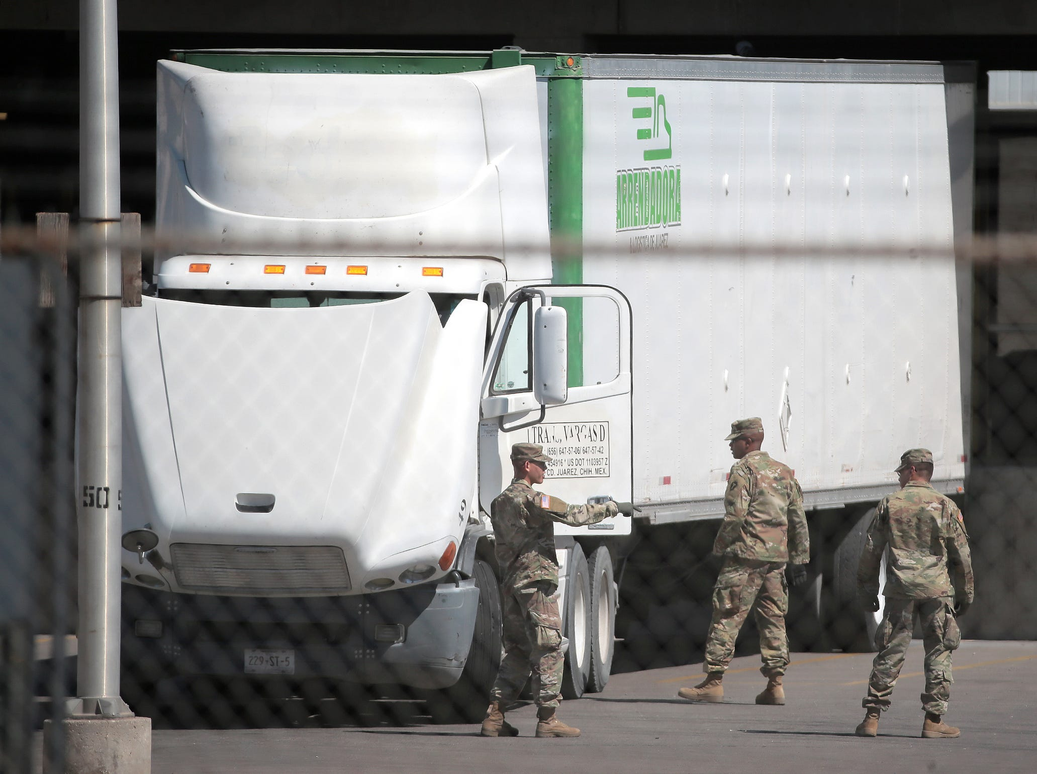 Soldiers inspect trucks at the Cordova Bridge Wednesday.