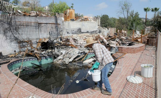 Steve Solomon, vector control technician with Ventura County Environmental Health Division, checks for mosquito larvae in a pool at a Bell Canyon home destroyed by the Woolsey Fire.