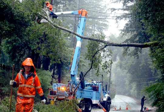 In this Jan. 8, 2017 file photo, a Pacific Gas & Electric Co. crew works to clear a downed tree over Highway 9 north of Boulder Creek.