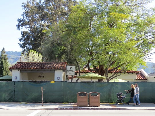 Passers-by stroll next to construction fencing at 469 E. Ojai Ave. in downtown Ojai. Formerly home to Knead Bakery, the site will reopen this spring as Ojai Rotie, a combination bakery, rotisserie and wine bar.