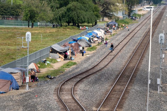 Dozens of homeless have set up shelters along the railroad tracks west of J Street between Prosperity and Cross avenues on Wednesday, April 3, 2019.