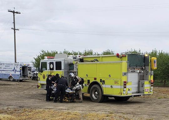 Fire and medical officials attend to one of two teenage boys who were electrocuted while trying to rescue a dog from an irrigation canal at an orchard in Dixon, California, on April 1, 2019.