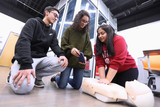 Ardsley High School twins Adeel and Amber Arif watch as Maanya Ravichandran practices CPR at the school April 2, 2019.