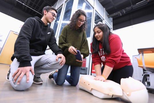 Ardsley High School twins Adeel and Amber Arif watch as Maanya Ravichandran practices CPR at the school April 2, 2019.